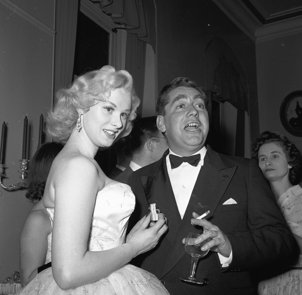 1955: Sabrina, Britain's answer to Marilyn Monroe, snatches a sandwich as she chats with British comic Tony Hancock during a function at the Royal Albert Hall in London. (Photo by Harry Kerr/BIPs/Getty Images)