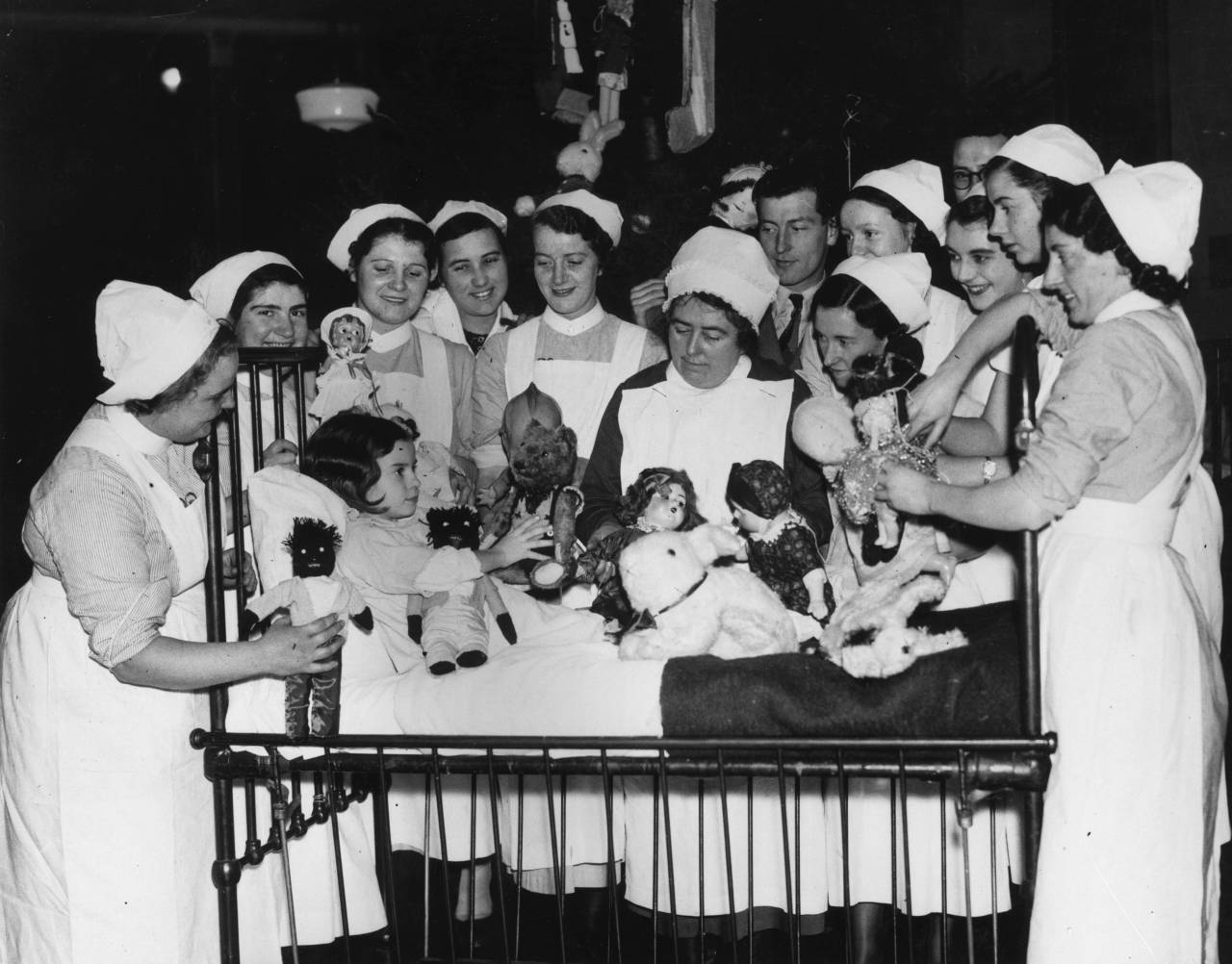 21st December 1937: Nurses at the Royal Infirmary in Cardiff's children's ward shower a young patient with toys for Christmas. (Photo by Fox Photos/Getty Images)