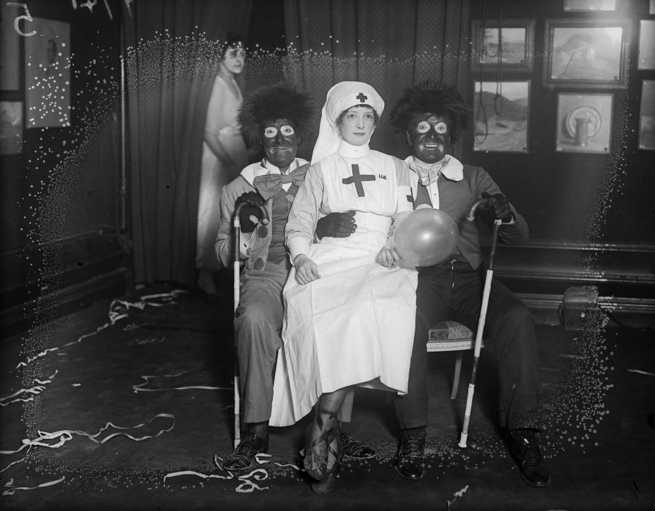 January 1919: Fancy dress for an 'American' night at Princes; a woman dressed as a nurse and two men in 'golliwog' outfits which are based on the appearance of a gallant hero in a series of children's books in verse by US writer Bertha Upton. (Photo by A. R. Coster/Topical Press Agency/Getty Images)