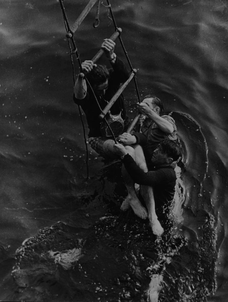 May 1940:  Three men being rescued from the sea after having to abandon ship as they were evacuated from the beaches at Dunkirk. They cling to a ladder let down by their rescuers.  (Photo by Picture Post/Hulton Archive/Getty Images)