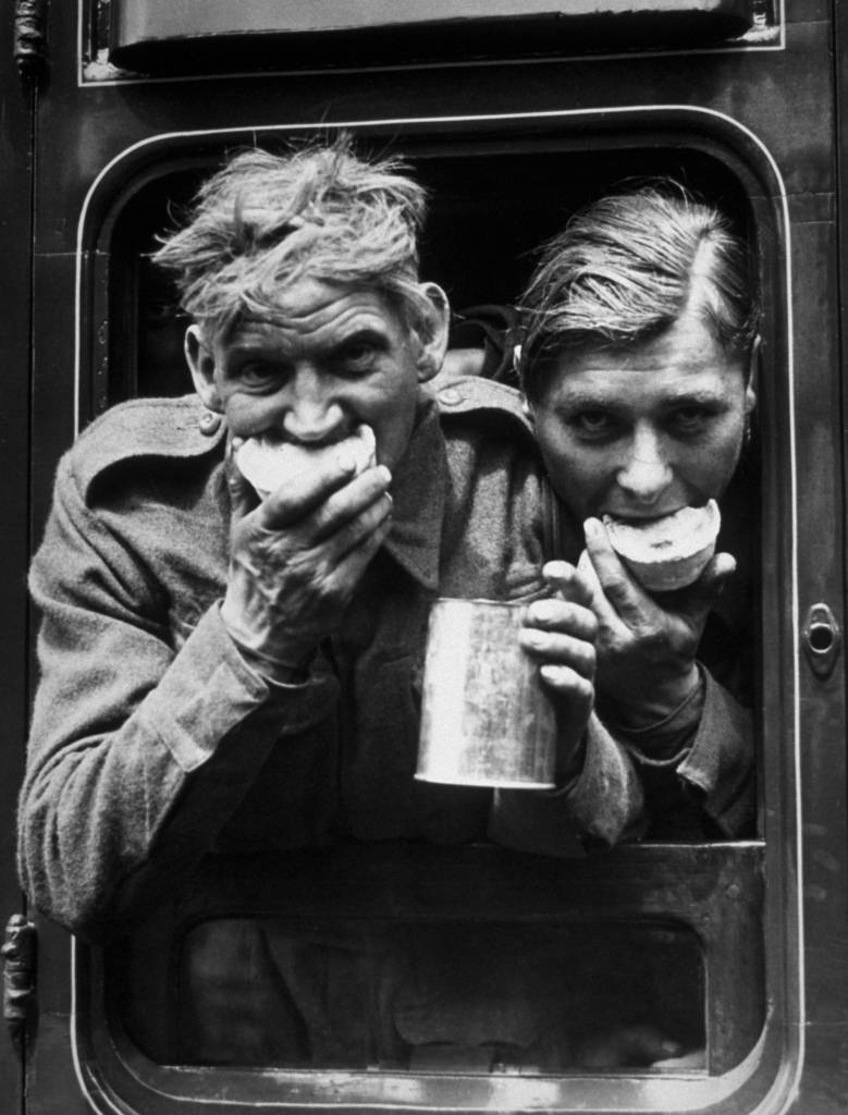 1940:  Two soldiers tuck in to the food and refreshment they received after their arrival in Britain, after evacuation from Dunkirk.  (Photo by Fox Photos/Getty Images)