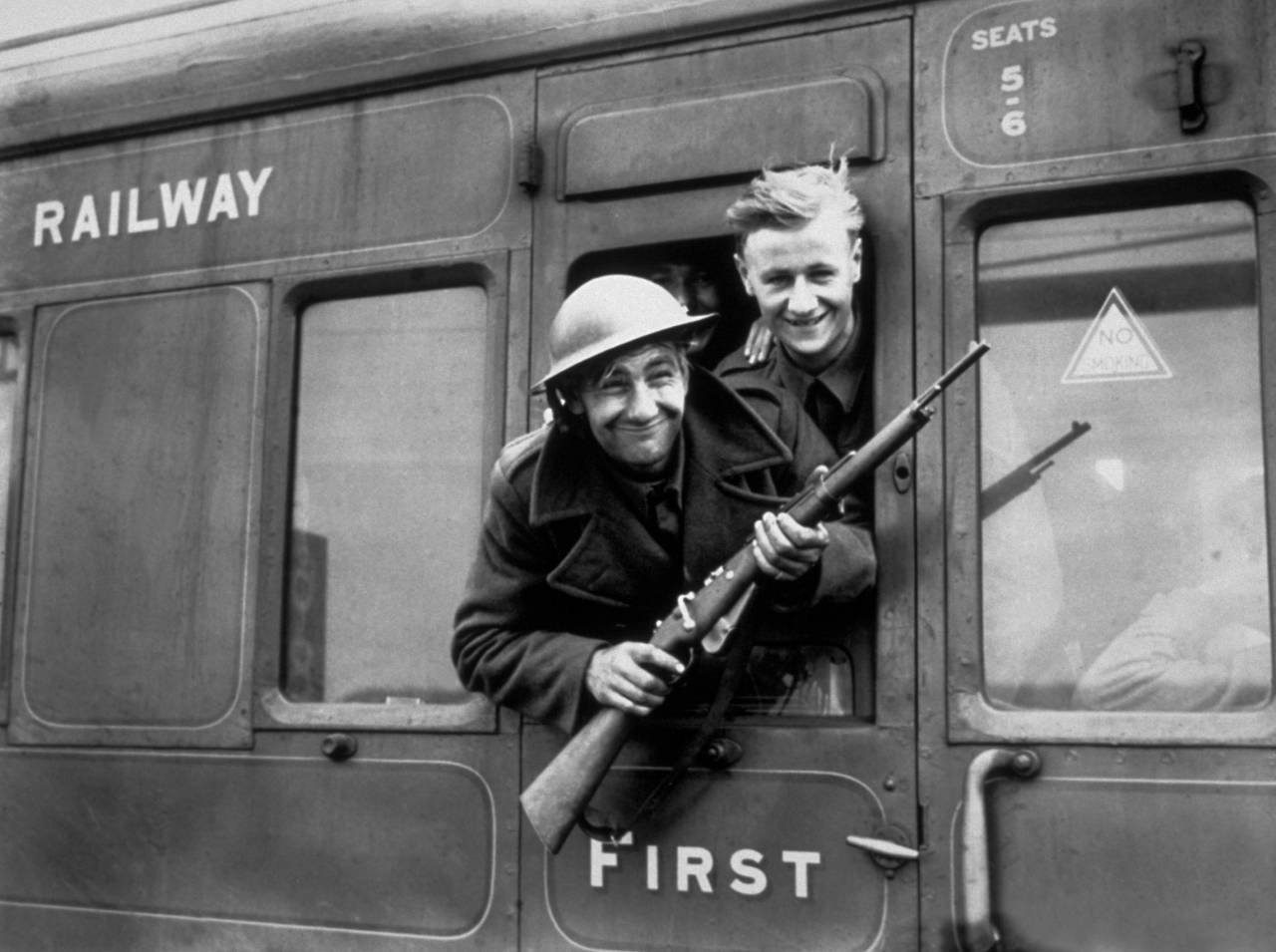 1940:  Troops continue to arrive home in their thousands following the rescue of the British Expeditionary Forces at Dunkirk. This member of the BEF has brought a German rifle home as a souvenir.  (Photo by Parker/Fox Photos/Getty Images)