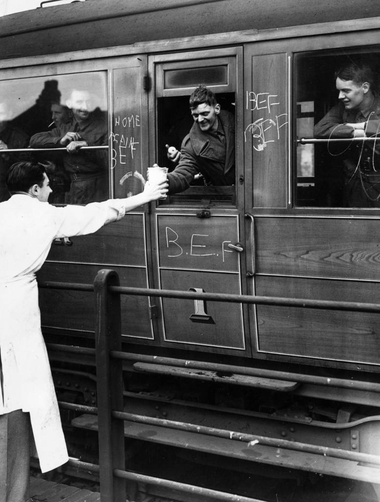 June 1940: Voluntary helpers give refreshments to wounded soldiers, members of the British Expeditionary Force, on board a hospital train. (Photo by J. A. Hampton/Topical Press Agency/Getty Images)
