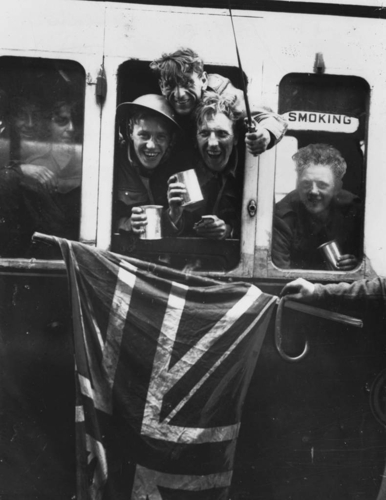 June 1940:  Members of the British Expeditionary Force arrive back in Britain with a Union Jack after being evacuated from Dunkirk.  (Photo by Keystone/Getty Images)