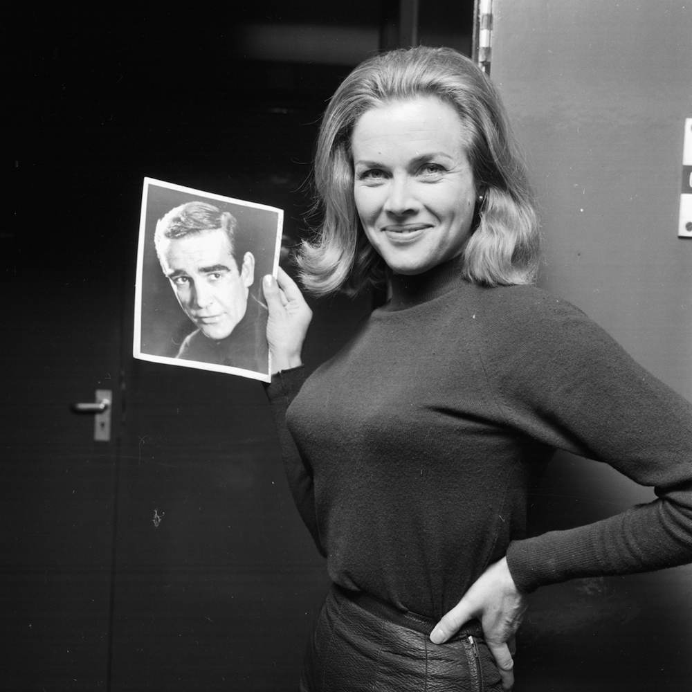 Portrait of actress Honor Blackman holding a picture of actor Sean Connery, following her being cast in the new James Bond film, 8th January 1964. (Photo by Larry Ellis/Express/Getty Images)