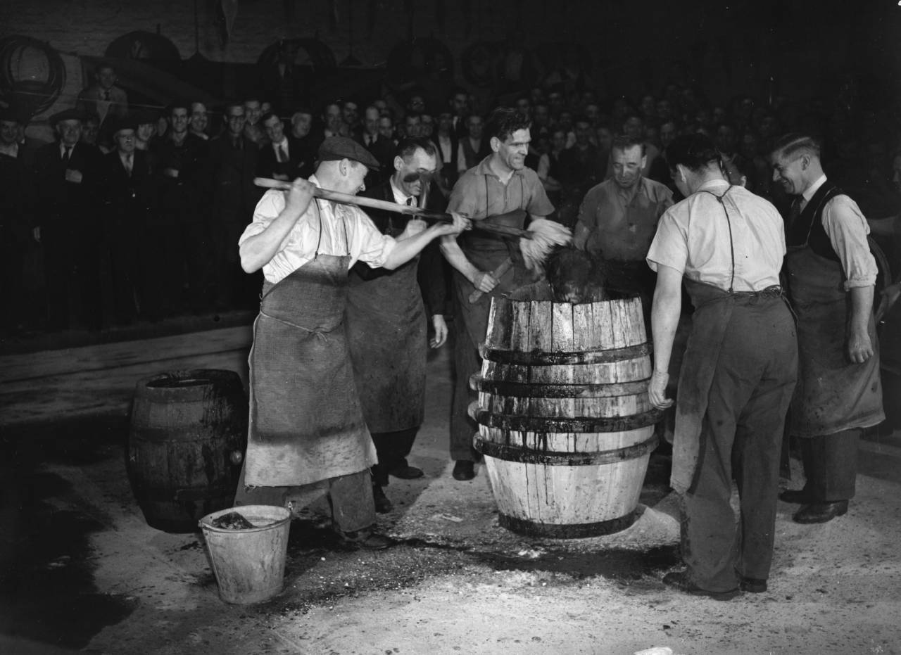 1st September 1950:  An apprentice cooper from Watney's Stag Brewery in Mortlake is put in a barrel and doused with soot, sawdust and beer at the brewery, by his workmates.  (Photo by J. A. Hampton/Topical Press Agency/Getty Images)