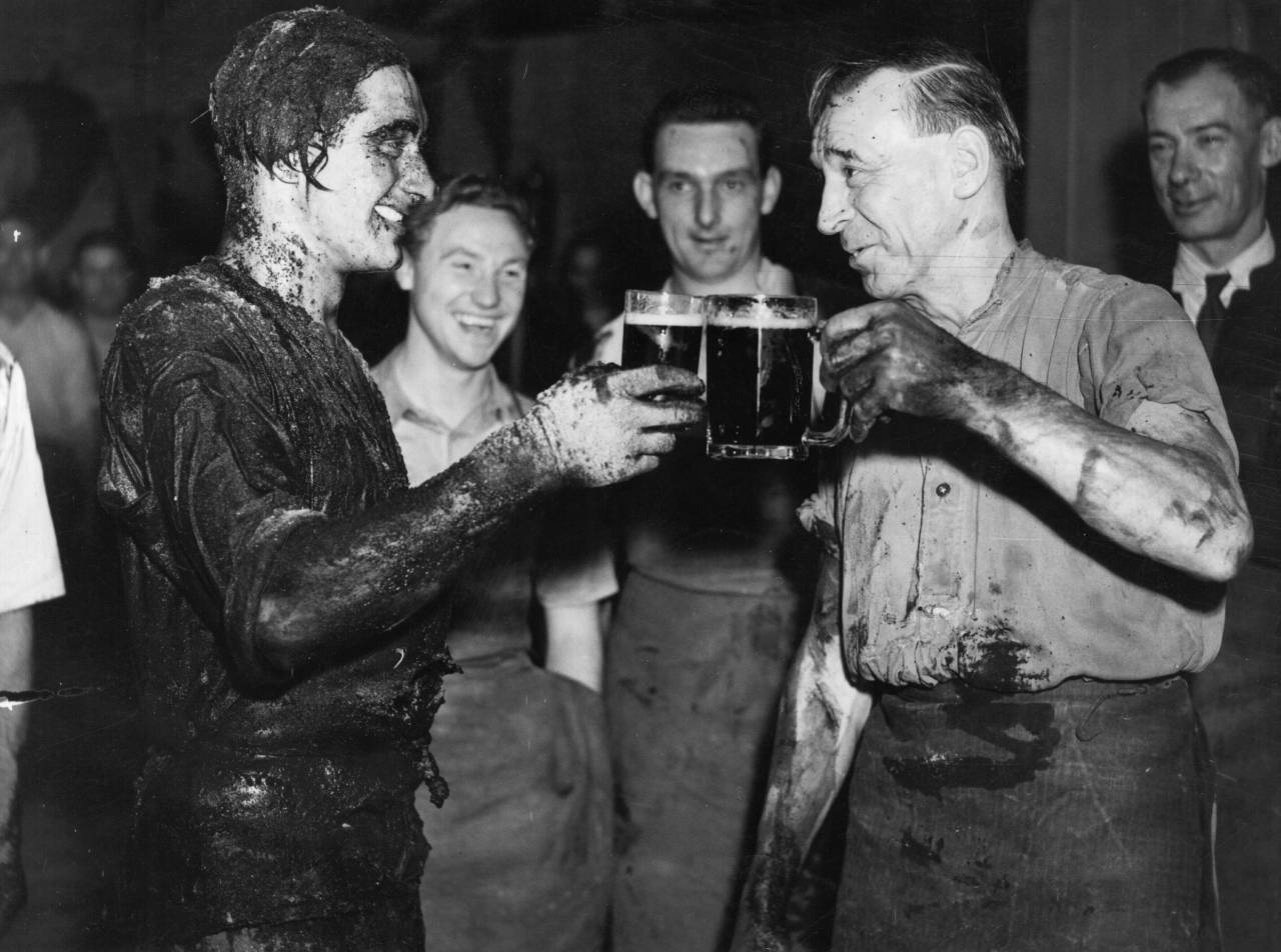 1st September 1950:  P Newton, right, toasting his pupil apprentice cooper R A Barban after his passing out ceremony at Watney's Stag Brewery, Mortlake, London. During the ceremony, called 'Trussing the Cooper',  the cooper is encased in his own barrel, has various concoctions including beer poured over him and is rolled around the brewery in the barrel.  (Photo by Topical Press Agency/Getty Images)