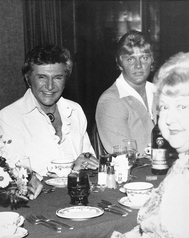 Entertainer Liberace, left, is seen with Scott Thorson, his bodyguard, chauffeur and confidant, at a Boston area restaurant in 1981. (AP Photo/Pete Anastasi)