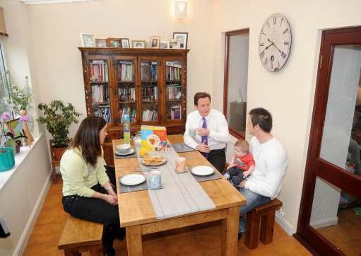 Conservative Party leader David Cameron discusses the cost of living over breakfast with a family (who asked not to be named), who benefit from Warmzone insulation in the Kirklees district of Huddersfield this morning.