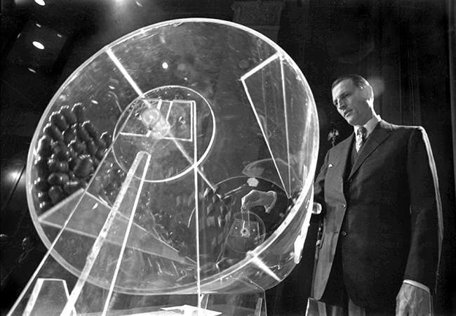 FILE - In this Feb. 2, 1972, file photo Draft Director Curtis W. Tarr spins a plexiglass drum containing capsules with birth dates and orders of assignments for men born in 1953 at the beginning of the fourth annual Selective Service lottery in Washington. Tarr, the man who developed the lottery for the draft during the Vietnam War, died Friday of pneumonia at his home in Walnut Creek, Calif., his daughter Pam Tarr said Wednesday, June 26, 2013. He was 88. (AP Photo, Charles W. Harrity, File)
