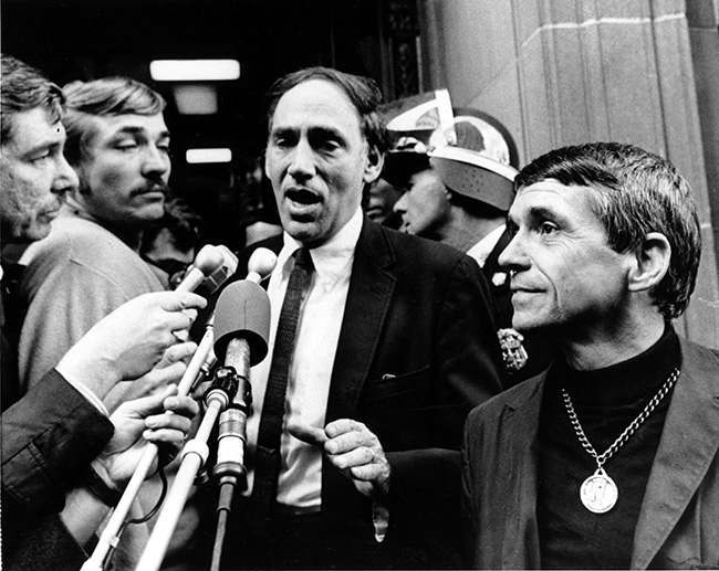 The Rev. Daniel Berrigan, right, and defense lawyer William M. Kunstler talk with newsmen after Fr. Berrigan and eight other Catholics were sentenced to two years to three-and-a-half years in prison in Baltimore, Md., on Nov. 9, 1968. Fr. Berrigan was convicted for burning Selective Service records to protest the Vietnam War. (AP Photo)