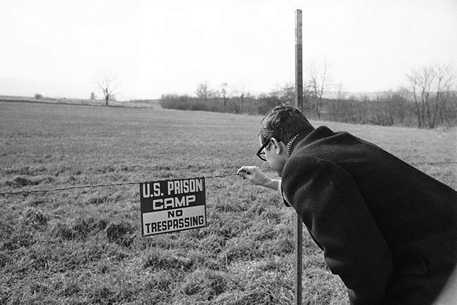 Newsman examines sign hanging from single strand of barbed wire that is only separation between minimum security federal prison at Allenwood, Pennsylvania March 7, 1969, and the outside world along one border of the sprawling prison camp. Security is so minimal that barbed wire is stretched only to keep camp's cattle herd from straying. Camp has been described by a civil rights lawyer as a detention camp for draft resisters. Of its 346 inmates about 90 have been convicted of Selective Service violations. (AP Photo/Bill Ingraham )