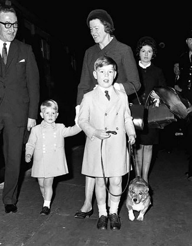 6 year old Prince Andrew with one of the royal corgis, and his 2 year old brother Prince Edward arrive at King's Cross Station, London, after an overnight journey from Aberdeen.