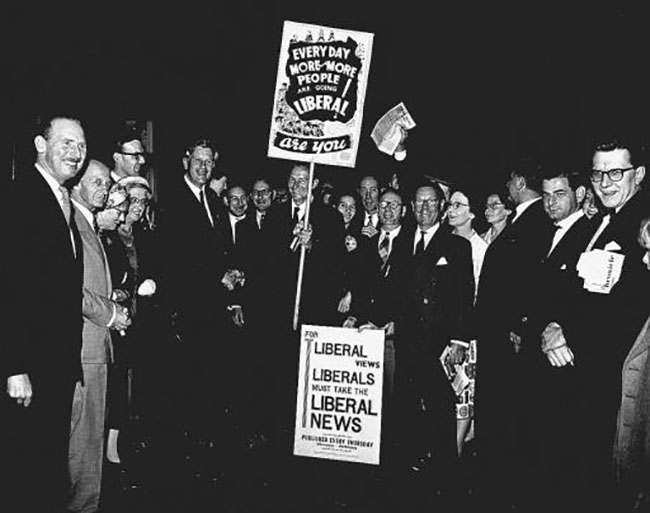 The leader of the Liberal Party, Mr. Jo Grimond, is greeted by Mr. David Brooke (shaking hands and holding placard) and other Liberals, notably Mr. Robin Day ( far right), on Mr. Grimond's arrival at King's Cross station, London, from Aberdeen. Mr. Grimond has left his constituency, Orkney and Shetland, to open the Liberals' general election campaign with a meeting at the Central Hall, Westminister, London.