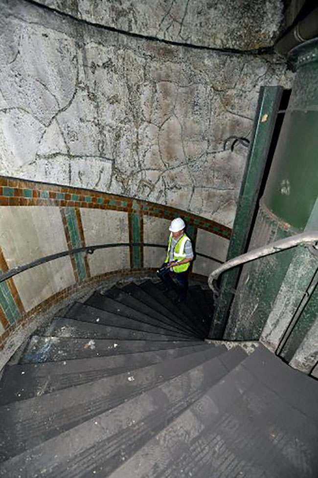EMBARGOED TO 0001 AUGUST 7. Ministry of Defence property surveyor Julian Chafer, ascends the spiral stairwell in the former Brompton Road tube station, a disused station on the Piccadilly line between South Kensington and Knightsbridge which is owned by the Ministry of Defence and which has been put on the property market.