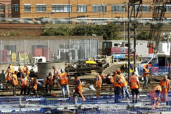 Maintenance workers labour to repair the track outside King's Cross Station, London, after Tuesday's derailment of a passenger train.