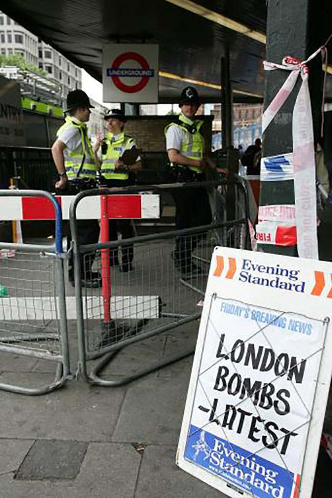 Police officers guard the entrance to King's Cross underground station, Friday, July 8, 2005. Commuters in London reluctantly descended into the Underground on Friday morning, attempting to return to routine in the aftermath of four rush-hour blasts that killed at least 50 people Thursday. Police said the attacks had the signatures of the al-Qaida terror network. (AP Photo / Sang Tan)
