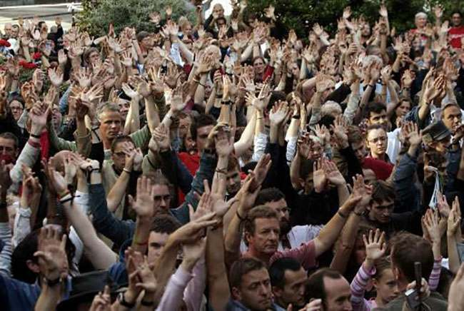 People join hands in remembrance of the victims of Thursday's London bombings, during a commemoration in a park near King's Cross station in central London, Saturday July 9, 2005. Police revised the timing of the deadly blasts that tore through the London Underground, saying on Saturday the explosions were detonated just seconds apart and were so powerful that none of the 49 dead have been identified and bodies remain trapped deep inside a subway tunnel. Hundreds have been reported missing. (AP Photo/Lefteris Pitarakis)