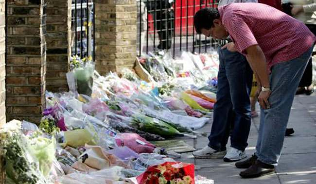 An unidentified member of the public reads floral tributes laid outside King's Cross train station in London, Sunday July 10, 2005 in memory of those that lost their lives and were injured as a result of the London bombings on Thursday July 7, 2005. A bomb exploded on the underground line between Russell Square and King's Cross underground stations Thursday. The bombing attacks killed 49 people and injured 700. (AP Photo/Jane Mingay)