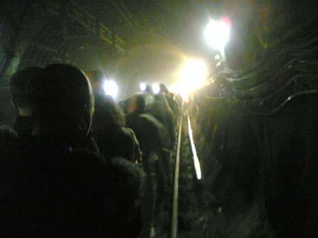 ** FOR USE AS DESIRED WITH YEAR END--FILE **In this image provided by commuter Alexander Chadwick, taken on his mobile phone camera, passengers are evacuated from an underground train in a tunnel near Kings Cross station in London in thisfile photo, following a bomb explosion.