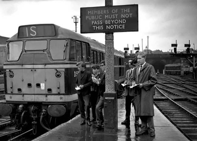 Young train spotters take down locomotive numbers at London Kings Cross station.