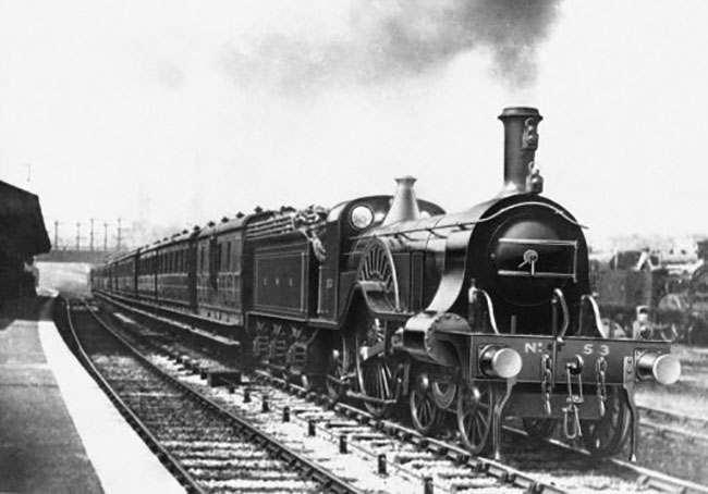 'The Flying Scotsman' , probably the world's best known train, celebrates it's centenary today (Monday) and here is the train as it passes Holloway Station (closed in 1915) between King's Cross and Finsbury Park. It is being drawn by a Great Northern Railway Stirling 8-footer No.53 (built in 1875).