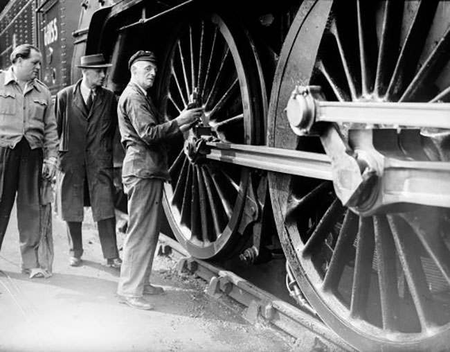 TV presenter Richard Dimbleby, left, watches the driver of the 'Night Scot' locomotive oil the wheels, at Kings Cross Station.
