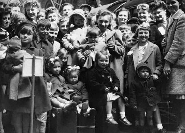 """The official return of 100,000 Londoners to their homes began oJune 4, when the first """" Devacuse"""" train arrived at St. Pancras station bringin 800 mothers and children from Leicester. Buses awaited to take the mothers and kiddies to dispersal centres where, after a hot meal, they went to their homes. Some of the mothers and children after de-training at St. Pancreas in London on June 4, 1945 waiting to board buses for dispersal points. (AP Photo)"""