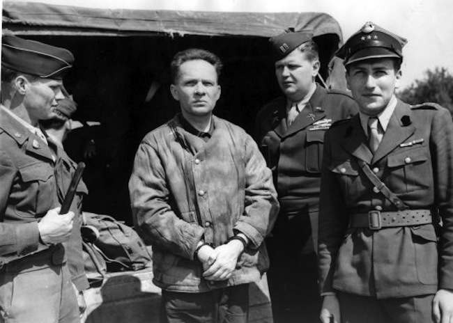 German Nazi commandant to be tried by Poles. Rudolf Hoess, self-confessed slayer of two and a half million jews as commandant of the Auschwitz extermination camp, is pictured at Fuerth Airport near Nuremberg. He will be tried at Warsaw along with Dr. Kurt von Burgsdorff, former governor of Kracow, and other German Nazis for crimes against humanity. They had been held at Nuremberg as witnesses at the International War Crimes Tribunal. AP-Photo shows: Rudolf Hoess handcuffed at Fuerth airport before boarding plane for Warsaw.With him, left to righ, are: - S/Sgt. Edge McGehee of Atlanta, Ga., Guard; Rudolf Hoess; Capt. S.H. Binder of Woodbine, Iowa, Operations Officer of I.M.T. Security; and Capt. Grodecki, Polish Army Representative.