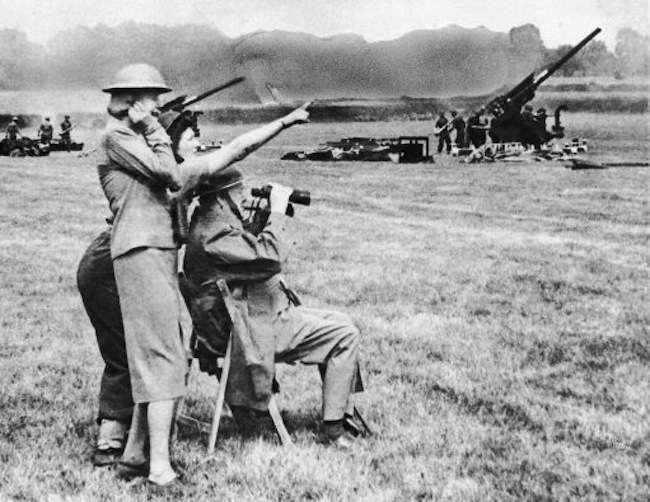 Prime Minister Churchill (seated) lifts his binoculars when his daughter Mary (behind him) points out a flying bomb at which a defense battery is firing, July 5, 1944. Mrs. Churchill holds her ears. The Churchill family made an inspection tour of Southern England flying defenses. (AP Photo)