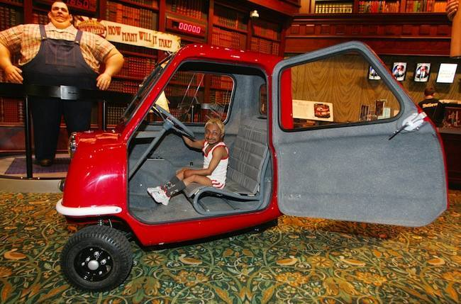 Romeo Dev, the world's smallest bodybuilder sits in a Peel P50, the world's smallest car, for the launch of two weeks of Olympic fun at Ripley's Believe It or Not! attraction in Piccadilly Circus, London.