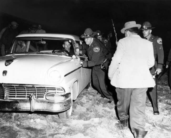 Highway patrolmen help a man out of a field where a Ku Klux rally was to be held, Jan. 18, 1958. A gun battle took place between whites and Indians after a schedule Klan rally failed to get under warpath after a cross was burned in front of an Indian.