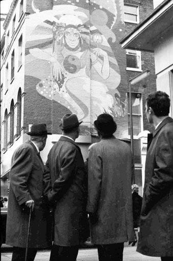 A group of men pause to look at the painting on the wall of the The Beatles shop, 'The Apple', in Baker Street, London, Dec. 6, 1967. (AP Photo/Staff/Harris)