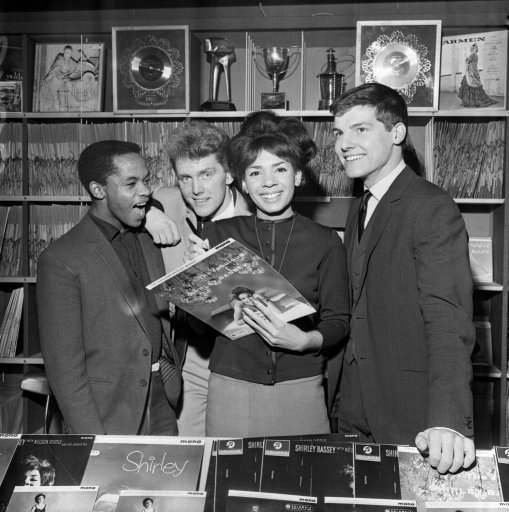 Singing star Shirley Bassey autographs the sleeve of one of her own records at the opening of the Shirley Bassey Record Shop in West End Lane, London. Looking on are pop singers (l-r) Danny Williams, Shane Fenton and Jess Conrad. Shirley's record shop is an extension of a bookshop owned by her husband, film producer Kenneth Hume. After finishing her season at the Talk of the Town, Shirley Bassey will leave for New York for a five week engagement in the Persian Room at the Plaza Hotel. This will Be followed by a four week season in cabaret in Sydney Australia.