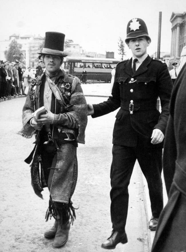 A policeman escorts a top hatted character after the law took over and ended the occupation by hippies of 144 Piccadilly street, London. PA/PA Archive/Press Association Images