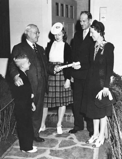Harvey Gibson, New York world's fair chairman, as he hands Mrs. Herbert woods of Ogden, Utah on May 27, 1940, a specially embossed lease to a model Fha-approved home where the woods family will live as the fair's guests for a week. Left to right: Herbert Woods, Jr., Gibson, Alice Woods, Woods and Mrs. Woods. (AP Photo)