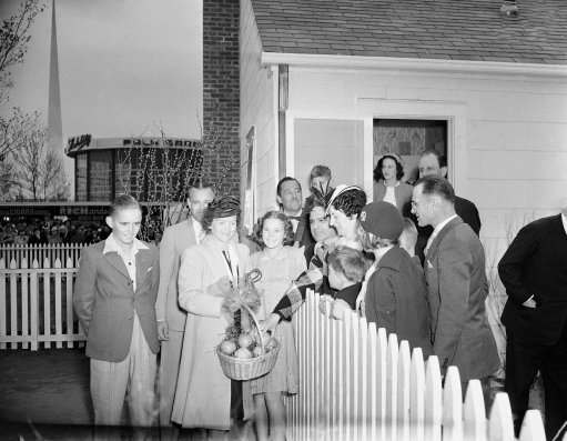 First of 48 families from every state to occupy homes at the New York world's fair was the Howard L. Burdin family of Miami, Fla., as the 1940 exhibit opened on May 11, 1940. Shown, on left side of front fence at the home, are, left to right, Jimmy Burdin, 14; Howard Burdin, Mrs. Howard Burdin and Elsie, 12. Over the fence to right, greeting the family, are, Grover Halen, President of the fair, Mayor F.H. LaGuardia of New York and his family and Joseph P. Moushey of Seattle, Wash., and his family, who were first occupants of another home. With Mr. and Mrs. Moushey are Joseph, Jr., 12 and Herbert, 5. (AP Photo)