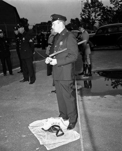 A policeman stands over the holster and revolver of one of two detectives who were killed by a bomb, found in the British Pavilion at the New York world?s fair on July 4, 1940, which exploded as officers examined it in the rear of the polish exhibit. The holster and most of the clothes were torn off one of the detectives by the flame-throwing bomb. Five others were injured by the blast.
