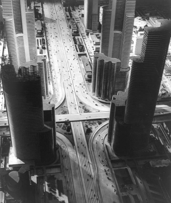 Futurama, the model city of 1960, designed by Norman Bel Geddes for the General Motors Exhibit at the New York World's Fair in 1939. This photograph shows an elevated view of the huge model of a futuristic city with widely spaced skyscrapers, double-decked streets with moving cars representing traffic patterns, and parks and landing pads for helicopters and auto-gyros shown on the roofs of low buildings.