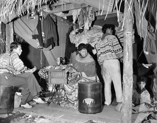 A group of Seminole Indians from the Florida Everglades have pitched their camp at the New York World's Fair where they loom as one of the attractions of the amusement zone, April 25, 1939. A family scene in one of the native huts, where an ancient sewing machine adds a modern note. (AP Photo)