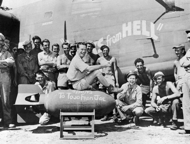 "Film actor Joe E. Brown autographs a 1,000-pound bomb, '""To Tojo from Joe,'"" and says, ""There, boys, is the address with U.S. forces somewhere in New Guinea on April 15, 1943. Now go and deliver it."" He is with the crew of the heavy B-24 bomber which is named ""Yanks from Hell.'"" (AP Photo)"