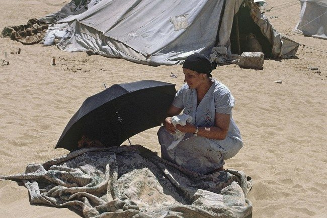 A lot of poor Egyptians seek cure by burial them self in the Sahara sand, just next to the Giza pyramids shown in 1985. The treatment lasts 45 days and it costs only 20 US dollars for the all treatment, and can be free for the very poor people. Khamis Abdel Motagally the founder of clinic in middle of the desert, learned from his father, the all family is convinced of its scientific basis. Treatment is part of the primitive natural medicine that originated with ancient Egyptians. His impormtu clinic comprises more than a dozen white tents on a dune at the back of the great pyramids of Giza West of Cairo, where he, and his sister and two other practitioners supervise the treatments. From a distance, the sandy hillside looks like a camp with umbrellas spouting from the sand, close up a visitor finds that beneath the umbrellas are people clutching thick blankets under the desert sun. People bury for 20-30 minutes wrapping themselves in thick blankets so they sweat more. Clothing is removed under the sand. At the end of the treatment they get massages, and hot soup to replace the liquid they loose in the hit. (AP Photo/Ciriani)