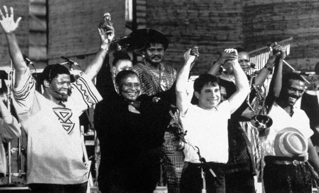 "American pop star Paul Simon, second right, joins hands with South African musicians Joe Shabalala, left, Miriam Makeba, second left, who has been exiled for 27 years, and Ray Phiri, during the first day on a two-day concert entitled ""Graceland in Concert,"" in Harare, Zimbabwe on Feb. 14, 1987. Blacks and whites from as far away as New York, Nairobi and South Africa attended the concert, the first public performance in Africa of Simon whose latest songs blend African rhythms with American pop music. (AP Photo)"