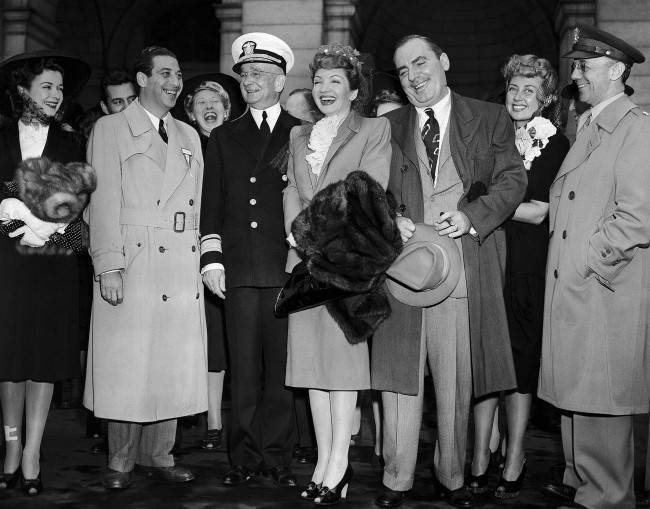 An honor guard of soldiers and Army and Navy officers greeted the 'Victory Caravan' of movie stars when they arrived at Union Station in Washington, April 29, 1942, for their first appearance on a tour for Army and Navy relief funds. Left to right are: Joan Bennett, producer Mark Sandrich, Charlotte Greenwood, in back, Rear Admiral Arthur J. Hepburn, Chief of the Navy Bureau of Public Relations, Claudette Colbert, Pat O'Brien, Joan Blondell, and Lt. Col. William Mason Wright, Jr., chief of the photographic section of the Army's Bureau of Public Relations. (AP Photo/Charles Gorry)