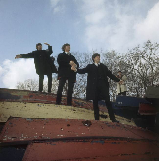 Three members of the Beatles pose on a stack of rowboats in New York's Central Park, Feb. 10, 1964. From top: Ringo Starr, John Lennon and Paul McCartney. (AP Photo)