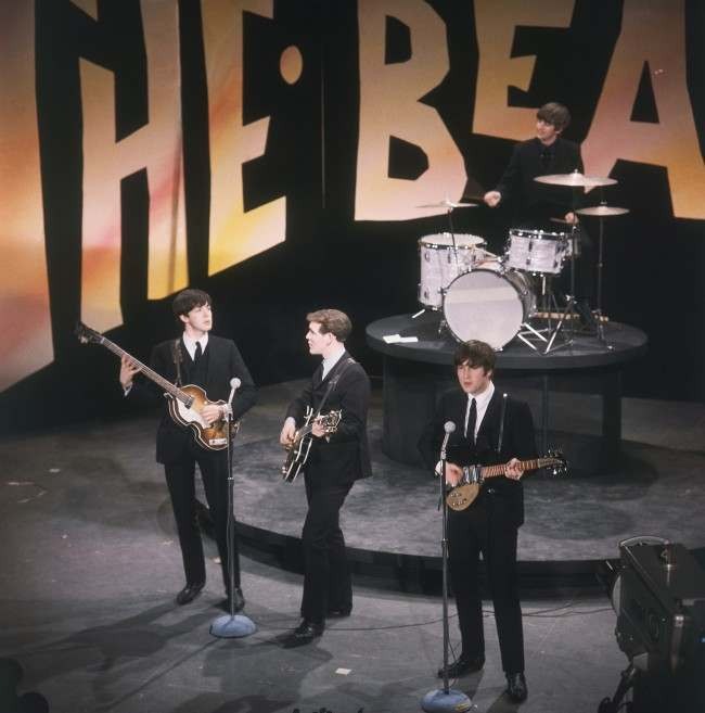 "The Beatles, minus an ailing George Harrison, perform on the ""Ed Sullivan Show"", Feb. 8, 1964. In front, left to right: Paul McCartney, Neil Aspinall (standing in for Harrison), and John Lennon. On drums is Ringo Starr. (AP Photo)"