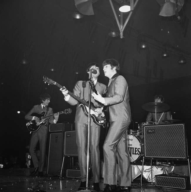 Surrounded by amplifiers and treading jumping beans underfoot, the Beatles swing into their routine during a show at the Coliseum in Washington, Feb. 11, 1964. From left: lead guitarist George Harrison, bassist Paul McCartney, rhythm guitarist John Lennon, and drummer Ringo Starr. The beans were thrown by excited fans. (AP Photo)