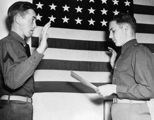 Lieut. E.L. Reid, personnel officer of the west coast training center at Moffett Field, California, right, swears in Jimmy Stewart, former movie star, as a second lieutenant in the Air Corps on Jan. 1, 1941. Stewart, who was one of Hollywood's most popular actors before he was inducted into the Army in 1941, was a corporal. (AP Photo)