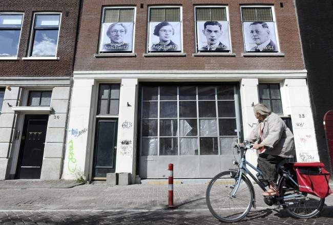 "Images of four Amsterdam Jews who died in the Holocaust are seen on a building on Kromme Waal street where they lived during the war in Amsterdam, Netherlands, Wednesday, May 4, 2011. A project called ""Jewish Houses,"" part of Wednesday's commemorations of World War II victims, encouraged Amsterdam residents to put up posters marking the 21,662 houses where Jews are known to have lived before the community was systematically sent to die in Nazi concentration camps. (AP Photos/ Evert Elzinga)"