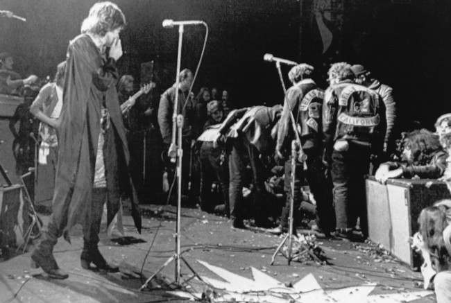 Mick Jagger stops performing at the Altamont Rock Festival at Livermore, California, Dec. 6, 1970, while Hells Angels cross stage during melee to help fellow motorcyclists. The Rolling Stones hired the Hells Angels to police the concerts for $500. (AP Photo)